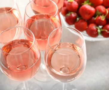 glasses of strawberry wine and a bowl of strawberries - How to Make Strawberry Wine Step-By-Step - Stone Family Farmstead